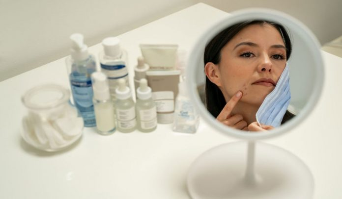 Woman struggling with mask and acne